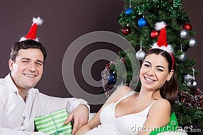 Happy pregnant couple near the christmas tree