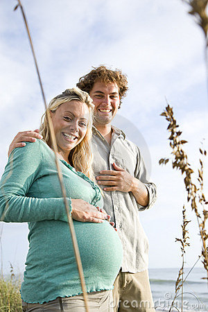 Happy pregnant couple standing together at beach