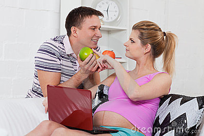 Happy pregnant family with fruit.