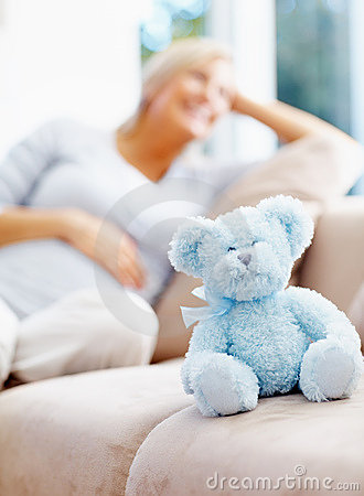 Happy pregnant female with teddy bear