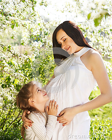 Happy pregnant mother and her little daughter