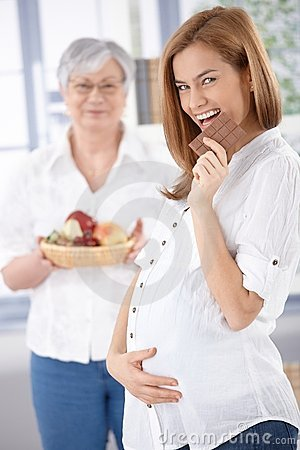 Happy pregnant woman eating chocolate
