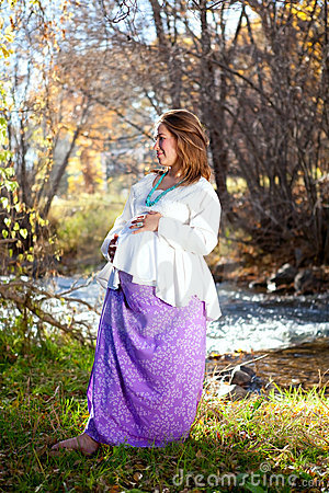 Happy pregnant woman in fall nature