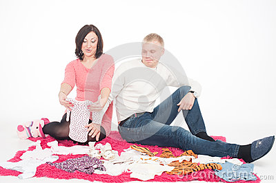 Happy pregnant woman with her husband looking at clothes for the