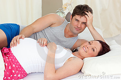 Happy pregnant woman lying on bed with her husband