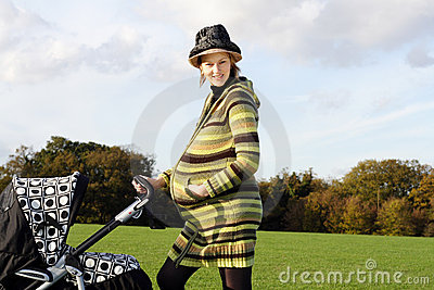 Happy pregnant woman pushing pushchair in the park