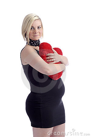 Happy pregnant woman with red heart shaped cushion