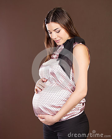 Happy pregnant woman touching her belly