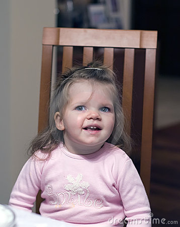Happy preschool girl in chair
