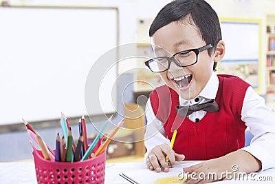 Happy preschooler draw with color pencils