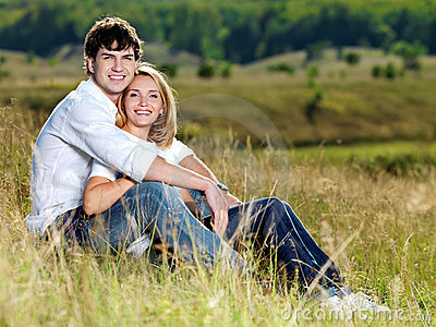 Happy pretty couple sitting in meadow