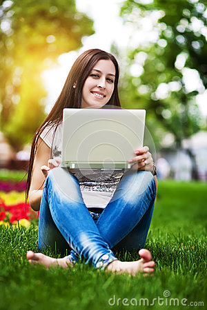Happy pretty girl sitting on grass with laptop