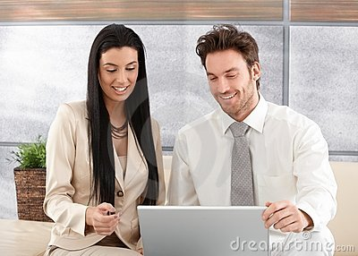 Happy professionals using laptop