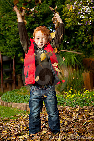 Happy red haired young preschool boy playing in au