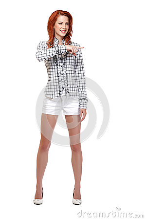 Happy redhead woman pointing at copyspace