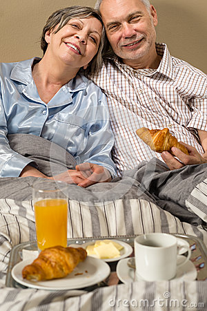 Happy retired couple eating croissant breakfast