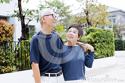 Happy retired senior Asian couple walking and looking at each other with romance in outdoor park and house in background. Stock Photo