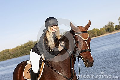 Happy rider caressing horse
