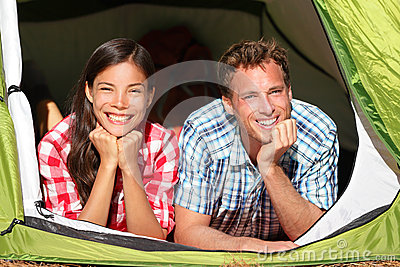 Happy romantic couple camping in tent looking