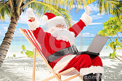 Happy Santa Claus on a chair working on a laptop and gesturing h
