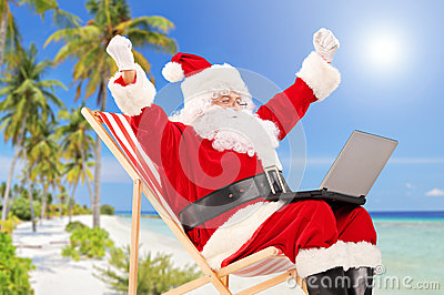 Happy Santa Claus sitting on a chair with laptop and gesturing h