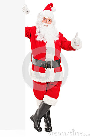 Happy Santa claus standing next to a billboard