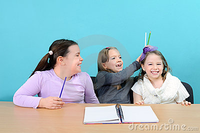Happy school girls making jokes in classroom