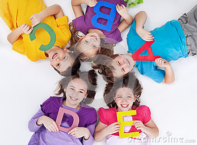 Happy school kids with colorful alphabet letters Stock Photo