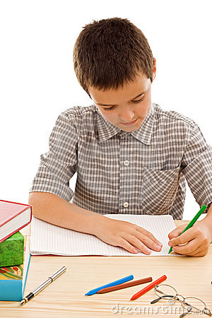 Happy schoolboy painting in the exercise book
