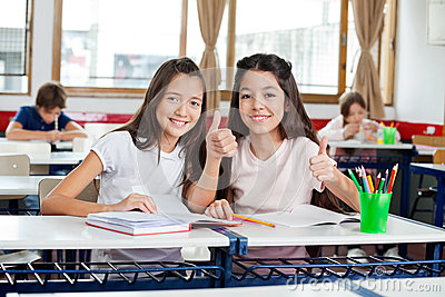 Happy Schoolgirls Gesturing Thumbs Up At Desk