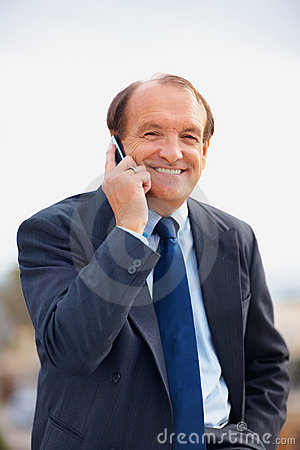 Happy senior business man using a cell phone