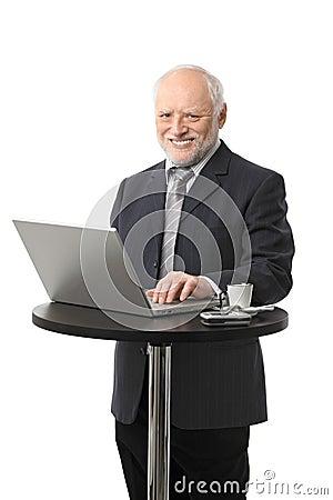 Happy senior businessman using computer