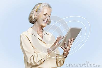Happy senior businesswoman using tablet PC against clear blue sky