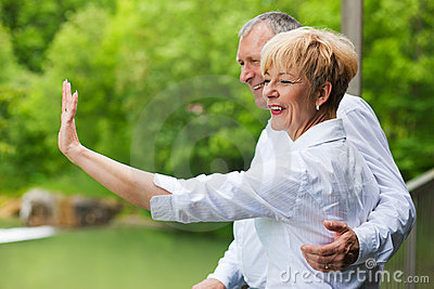 Happy senior couple on bridge waving hands