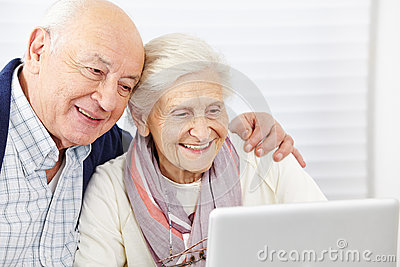 Happy senior couple with computer