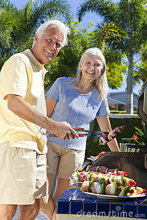 Happy Senior Couple Cooking on A Summer Barbecue