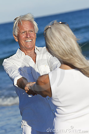 Happy Senior Couple Dancing Holding Hands Beach