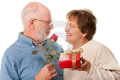 Happy Senior Couple with Gift and Red Rose