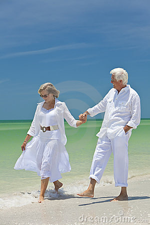 Happy Senior Couple Holding Hands on a Beach