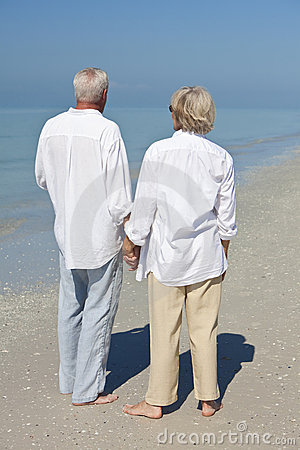 Happy Senior Couple Holding Hands on Beach