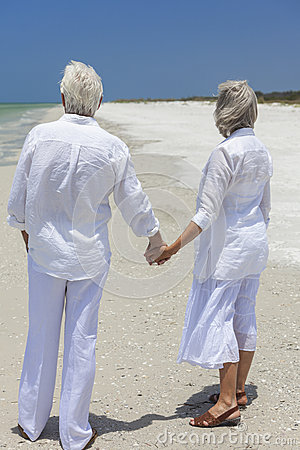 Happy Senior Couple Holding Hands on Tropical Beach