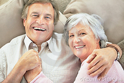 Happy senior couple lying together on the couch