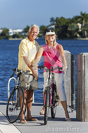 Free Happy Senior Couple On Bicycles By A River Stock Photography - 31391972