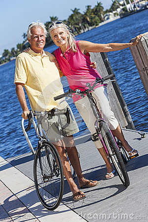 Free Happy Senior Couple On Bicycles By A River Royalty Free Stock Images - 31391979