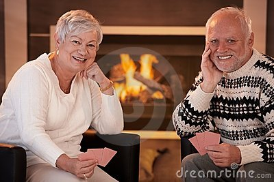 Happy senior couple playing cards at home