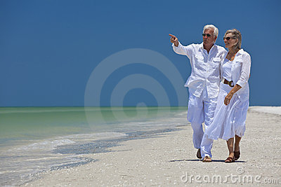 Happy Senior Couple Pointing To Sea on Beach