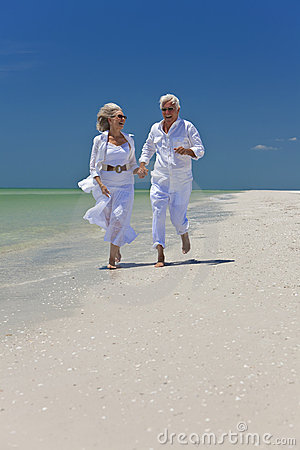 Free Happy Senior Couple Running On A Tropical Beach Stock Photography - 14436962