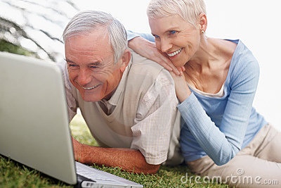 Happy senior couple using a laptop on grass