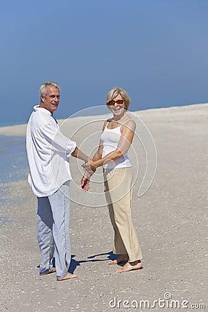 Happy Senior Couple Walking Holding Hands on Beach