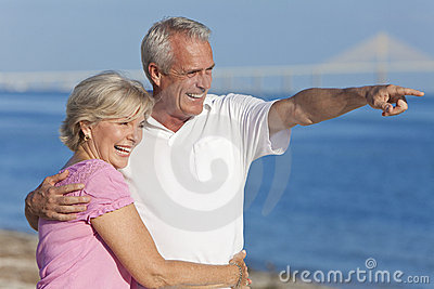 Happy Senior Couple Walking Pointing on Beach